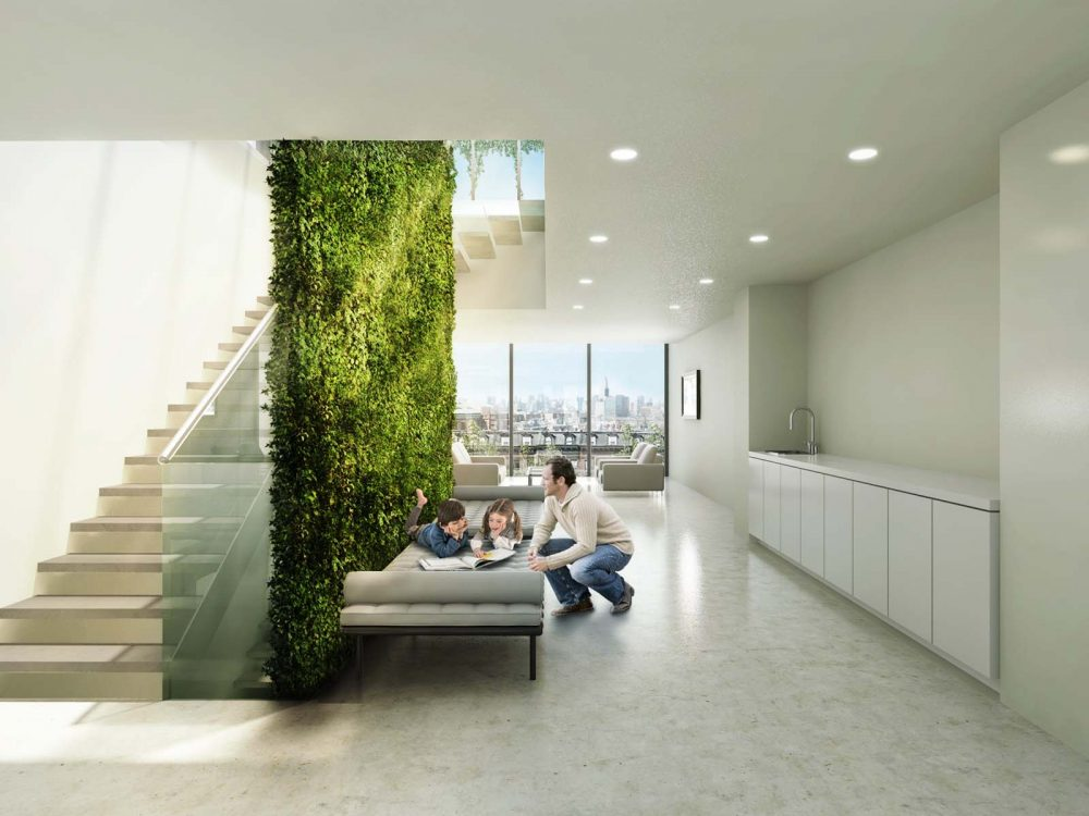 The interior space is filled with natural light from large windows, and color from the vertical green wall