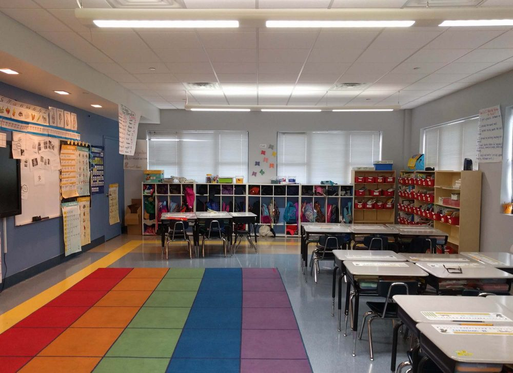 Classrooms benefit from natural light from multiple large windows, along with a variety of light fixtures